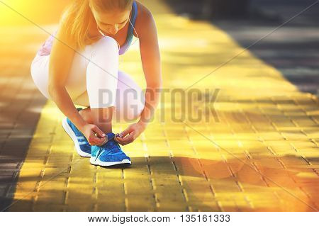 the woman athlete runner run and tying shoelaces