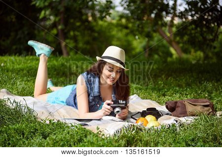 Joyful young woman is lying on blanket in the nature. She is holding a photo camera and smiling
