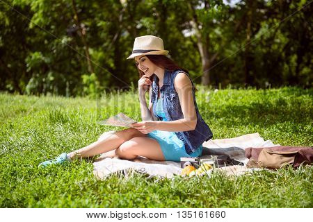 Cheerful female tourist is looking at guide map. She is sitting on blanket on grass and smiling