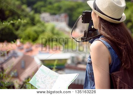 Curious girl is photographing city by camera. She is standing and looking forward with interest
