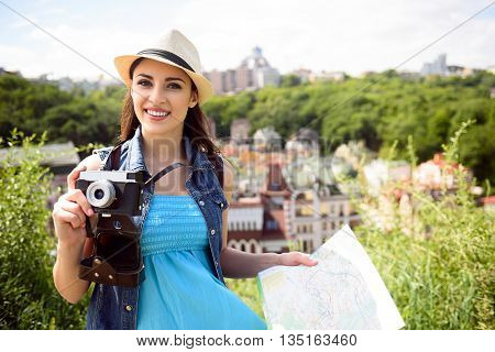 Joyful female tourist is traveling with map. Woman is taking photos by camera and smiling. Beautiful scenery of city on background