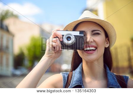 Happy young woman is taking photos of city. She standing and laughing
