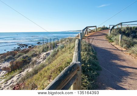 Pathway through the dunes overlooking the Murchison River and Indian Ocean river mouth point in Kalbarri, Western Australia with natural vegetated dunes and coastal rock on a clear day.