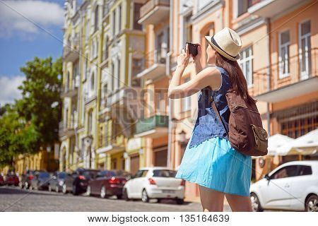 Happy female tourist taking shots of town. She is standing on street and smiling. Girl is carrying a backpack and camera