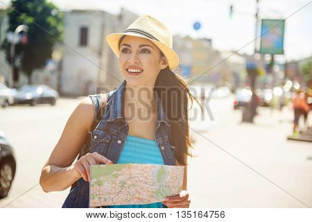 Attractive young girl is making journey across city. She is holding a map and laughing