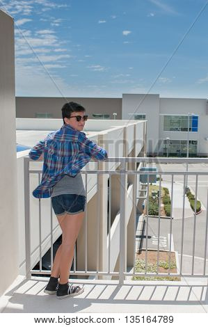 Teenage girl with crew cut leaning back on handrail under blue sky.