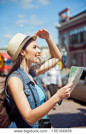 Happy girl is traveling across town. She is standing and holding a map. Girl is raising arm to head and looking forward with aspiration. She is smiling