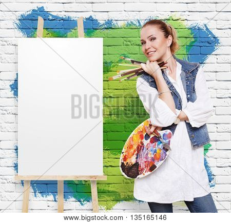 Art and craft. Woman artist with art tools. Girl painter with brushes and palette. Empty canvas at easel at colorful brick wall with copy space. Fine art. Art classes for adults, education concept.