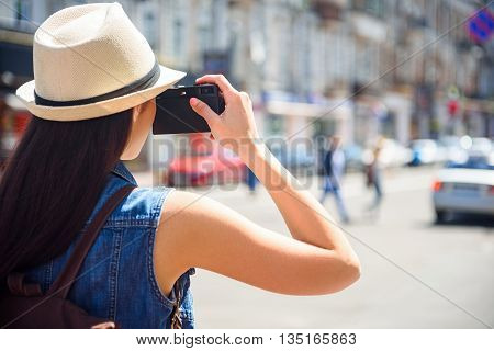 Curious female tourist is taking photos of city. Woman is standing and holding camera near her face