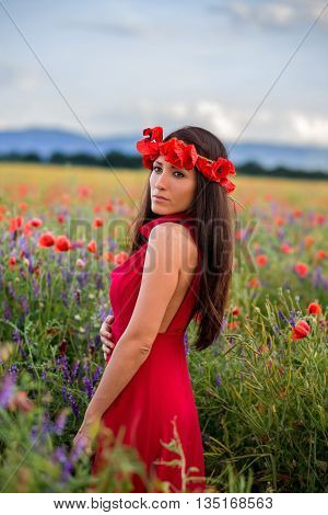 young girl with a beautiful dress in a field of poppies