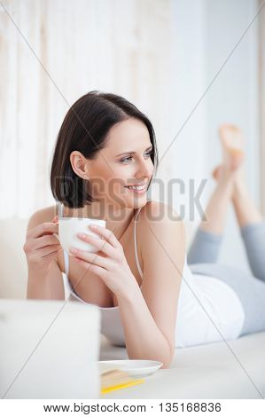 My idea of leisurely day. Attractive young woman drinking tea while reading book, lying on sofa