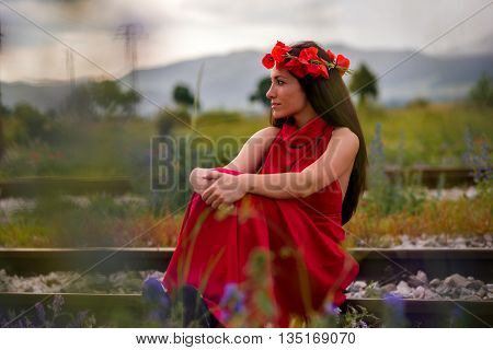 young girl with a beautiful dress on railroad tracks