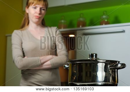 Pan on electric stove in the kitchen. Young woman annoyed, frustrated. Redhead woman cooking soup in home kitchen. Housewife looking in to pan.