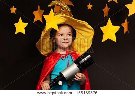 Beautiful little girl in sky watcher costume stargazing through a telescope