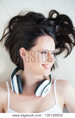 Relaxed tunes. Top view of smiling young woman with her headphones, lying on sofa