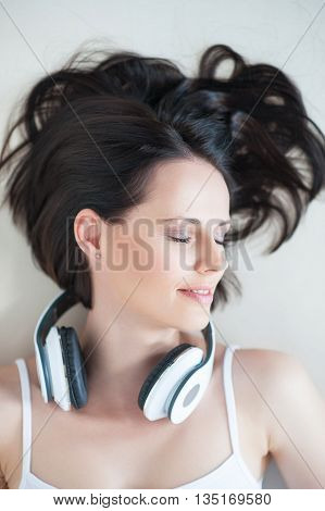 Lost in the music. Top view of attractive young woman lying on sofa with her headphones, with close eyes and dreaming about something