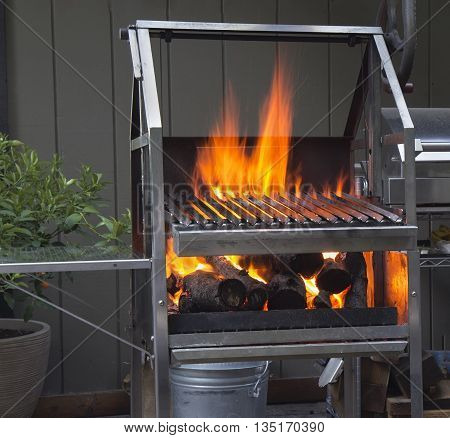 Grill with flame and firewood at backyard
