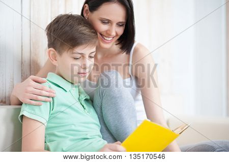 Useful time together. Close up of smiling mother and her adult son reading book, sitting on sofa
