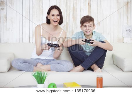 I still will be the first. Beautiful woman and her teenage son at home, sitting on couch and playing video game