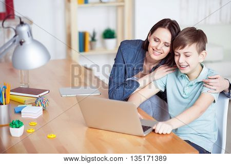 Making homework time happy time. Mother embracing shoulders of her son, working with laptop