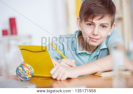 Homework at table. Close up cheerful young boy smiling while doing his homework