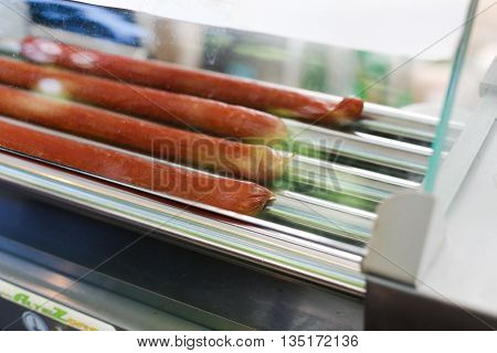 Hot dog machine closeup. Sausages grill at hot dog maker. Professional equipment for hot dog preparation. Various sausages, wurst at grill.