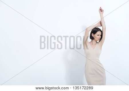 Feminine fashion. Attractive young fashion model posing in cream dress in studio and smiling, isolated on white background