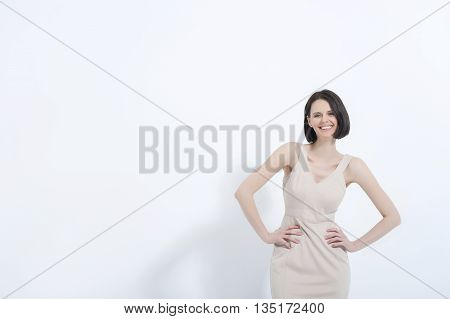 Looking good in her summer wear. Smiling woman posing sweetly in dress, isolated on white background