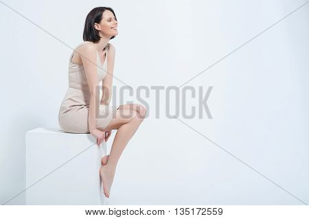 Carefree beauty. Beautiful young woman posing in cream dress on white cube at studio, isolated on white background