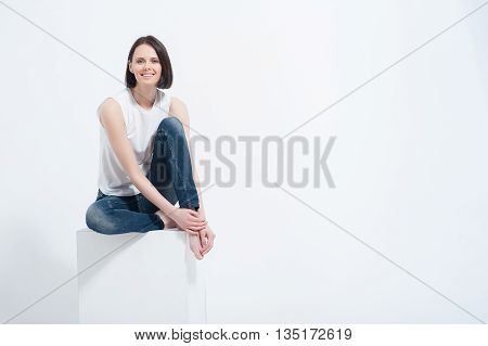 Starting her day off by looking great. Portrait of smiling woman wearing jeans and sitting on white cube, isolated on white background