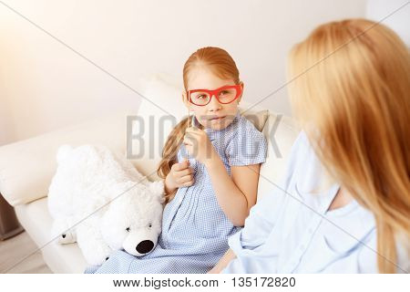 Browsing together. Shot of mother and young daughter sitting on sofa at home with paper glasses on sticks