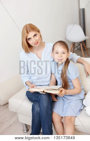 Let read story. Top view of young mother reading to her daughter at home, sitting on sofa