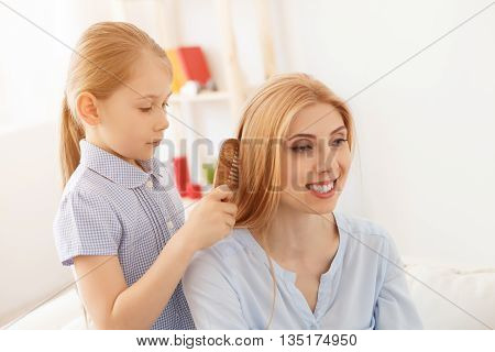 My mom is most beautiful. Close up of little girl brushing hair to her smiling mother at home