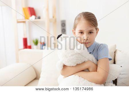 She loves her teddy. Portrait of cute little girl hugging her teddy bear, sitting on sofa