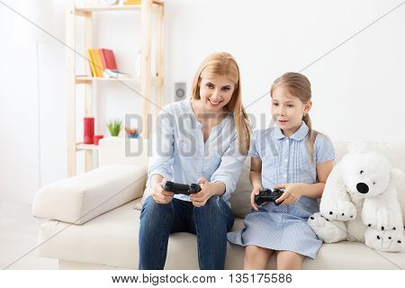 You always beat me. Smiling mother and daughter having fun playing video games at home
