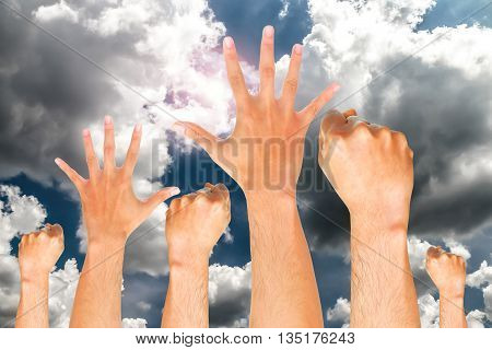Group of human hand showing fist on blue sky background with the sun, fish sign.