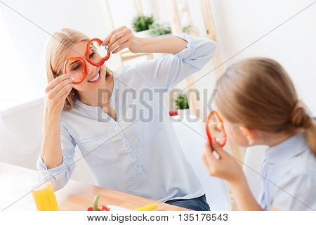 Spreading some creativity. Top view of smiling mother holding circles of red pepper near her eyes and looking at daughter