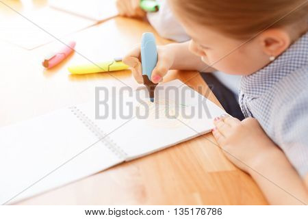 She loves her painting. Close up of little girl drawing flower in notebook using marker, sitting at desk
