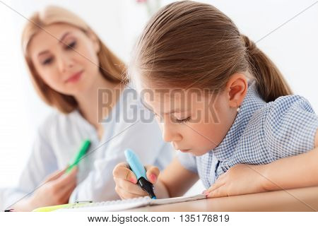 She is so creative. Close up of little girl drawing flower using marker, sitting at desk next to her mother