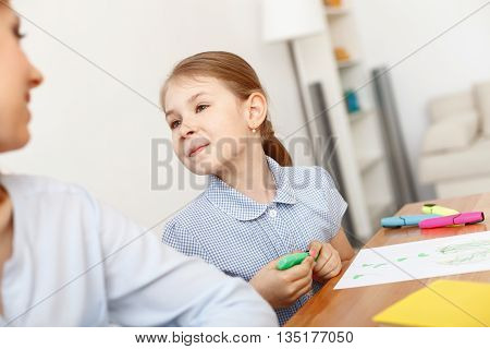 Creativity hard at work. Smiling little girl looking at her mother in drawing break