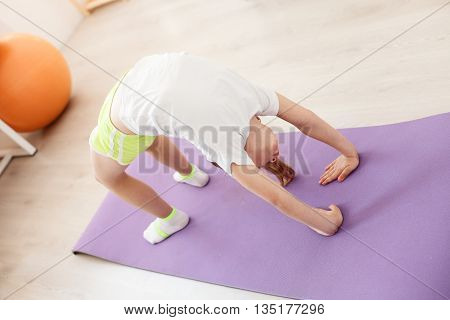 Look how I can. Top view of little girl doing gymnastics exercise on fitness mat