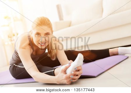 Yoga keeps her body flexible and strong. Smiling young woman doing stretching exercises at home