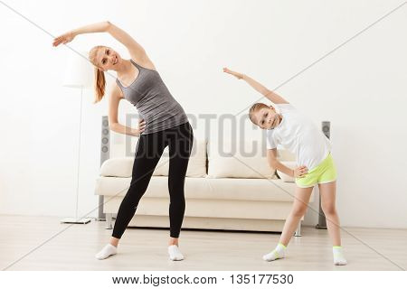 Her mother introduced her to yoga. Portrait of little girl and mother doing physical exercise at home