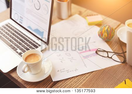 Concept workplace. Open laptop with a cup of coffee and papers on desk