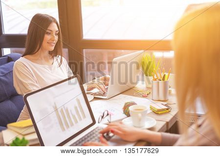 Happy young women are typing on laptops with concentration. They are sitting at table in cafe and smiling