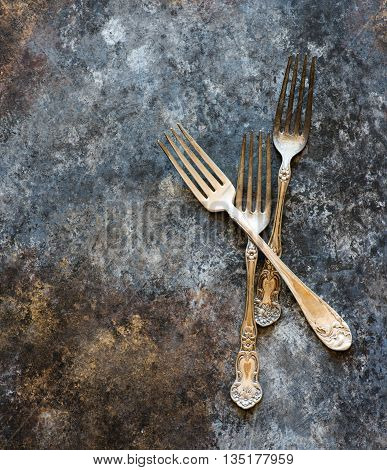 Vintage forks on rustic dark background top view