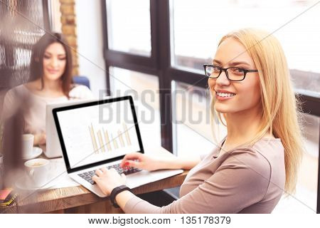 Successful young businesswoman is working with document on laptop. She is looking at camera and smiling. Her colleague is sitting at table on background