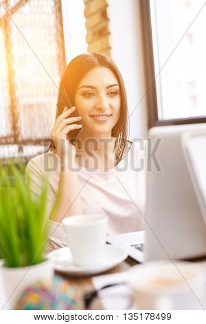 Happy young woman is talking on mobile phone in cafe. She is using a laptop and smiling
