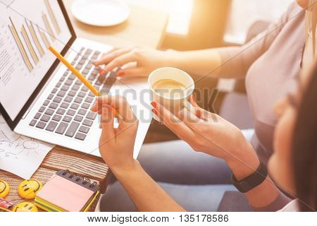 Concept of two smart colleagues discussing a project. Woman is pointing at laptop with inspiration. Her friend is drinking coffee