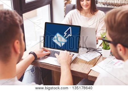 Smart young man is sending message on computer. He is sitting at the desk near his colleagues. Woman is smiling happily